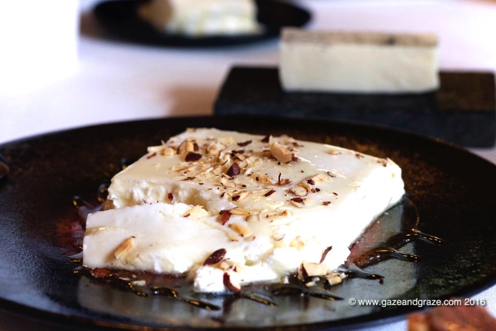 Cheese served with a sprinkle of nuts and oil